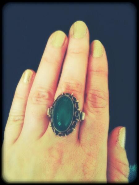 Goldener Nagellack und gruener Ring