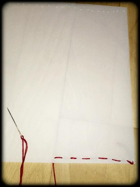 Pauspapier mit rotem Faden zusammengenaeht