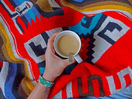 Tasse Kaffee auf bunter Decke