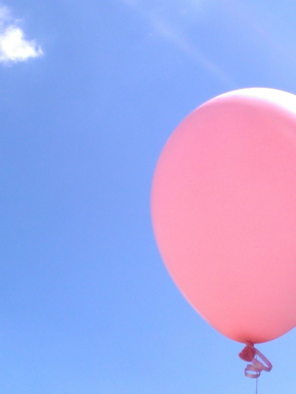 Pinker Luftballon vor blauem Himmel.