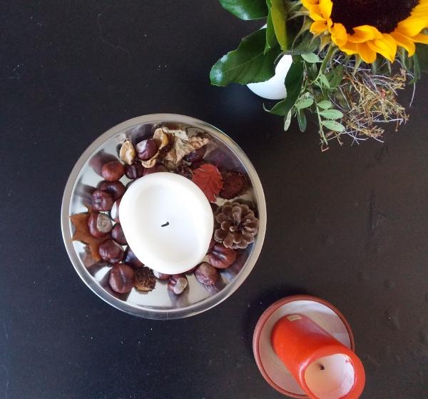Herbstdeko mit Kerze und Kastanien an Sonnenblume