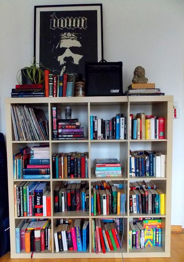 Volles Bücherregal mit Verstärker und Down-Poster oben drauf.