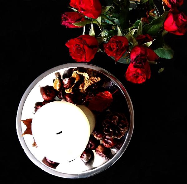 Rote Rosen neben weißer Kerze