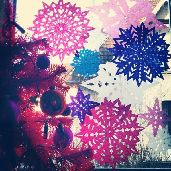 Weihnachtliches Fenster mit Papier-Eis-Sternen in Rot, Pink, Lila, Weiß und Blau, dazu ein roter Weihnachtsbaum